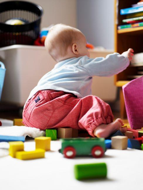 Enfant avec pantalon corail jouant avec des jouets en bois