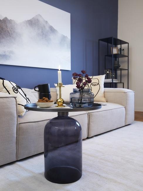 Blauwe wand met beige bank en tapijt met blauwe bijzettafel