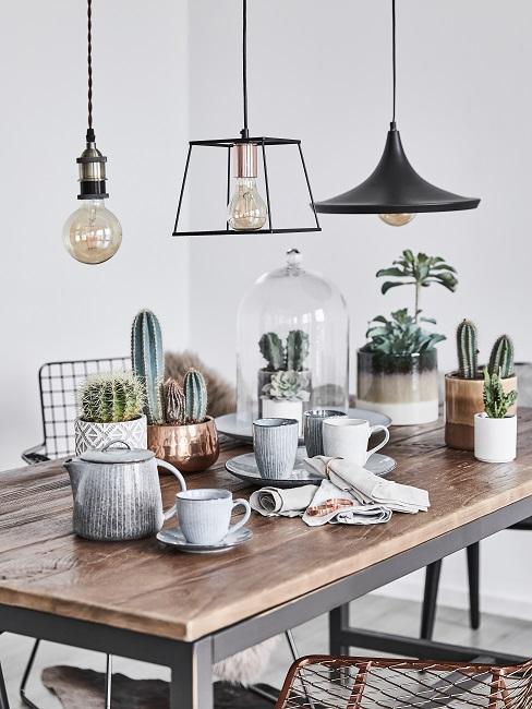 Tafel met industriële lampen, hippe plantenbakken en hout tafelblad.
