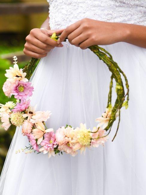 Bloemenkrans in de handen van een bruid