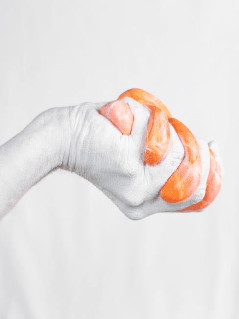 Oranje slijm in witte hand