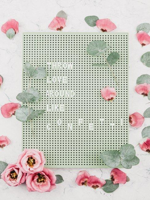 Pinbord met witte letters en bloemen