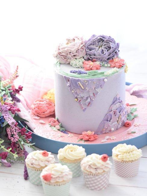 Paarse taart met witte cupcakes op roze schaal