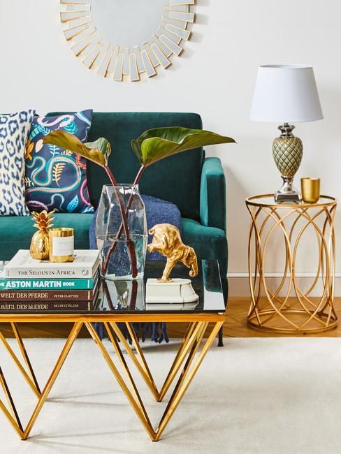 Smaragdgroen bank met gouden bijzettafel en salontafel voor witte muur