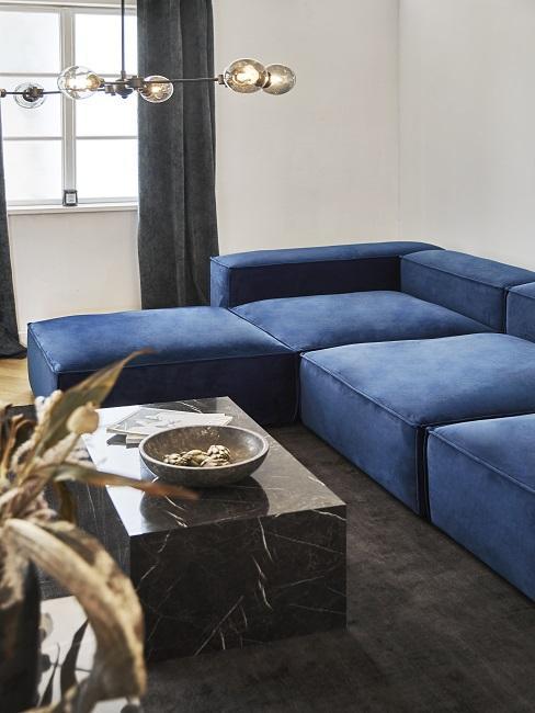 Hoekbank donker blauw met marmere salontafel op bruin tapijt