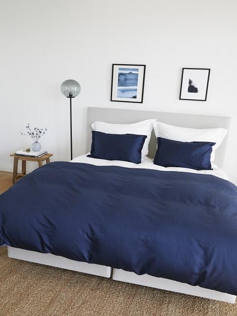 Slaapkamer met boxspring met donkerblauwe lakens
