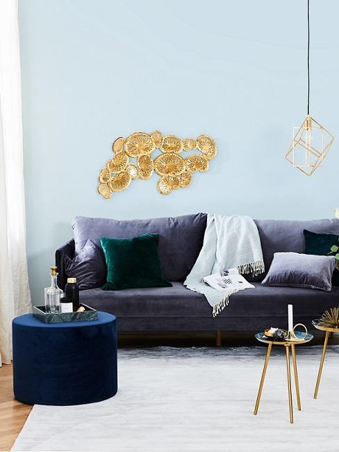 Licht blauwe muur met blauwe bank en gouden accessoires
