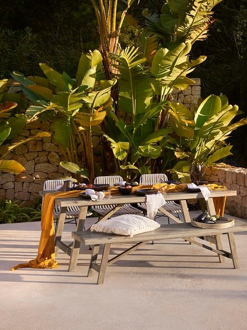 Bohemian tuin met grote banaanbladeren picknick tafel en bank met drie stoelen