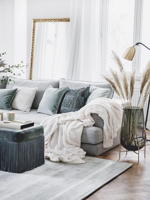 Bank met grijsgroene kussens, tapijt, velvet poef en mampasgras in vaas
