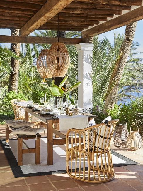 Bohemian tuin inspiratie lange houten tafle met bamboe stoel en lamp met witte lakes en details