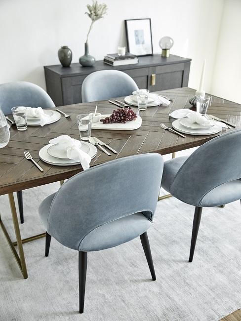 Grijs vloerkleed met donker houten tafel met lichtblauwe stoelen