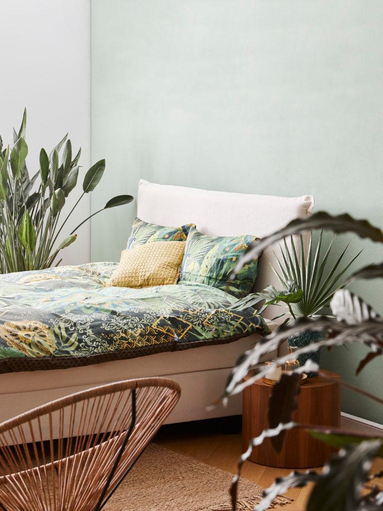 Slaapkamer met lichtgroene muur en wit bed met groene print lakens