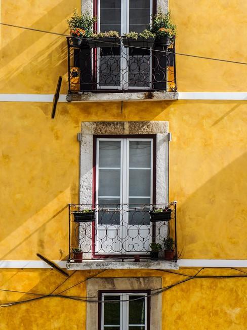 Geel huis met grote openslaande deuren als ramen met balkon