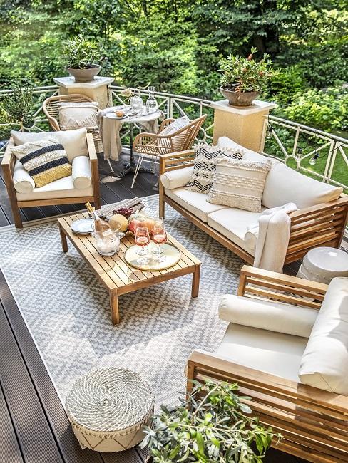 Tuinset van hout met witte kussens op grijs wit vloerkleed