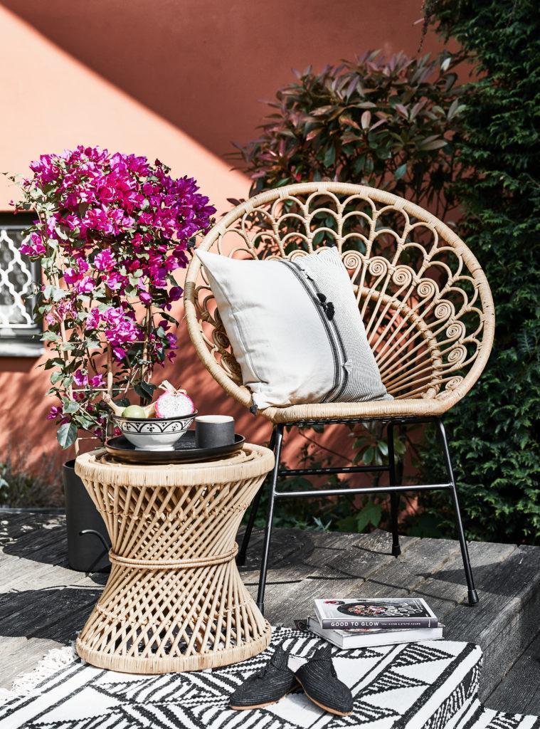 Zalm roze muur met rotan loungestoel en rotan bijzettafel op houten vlonder