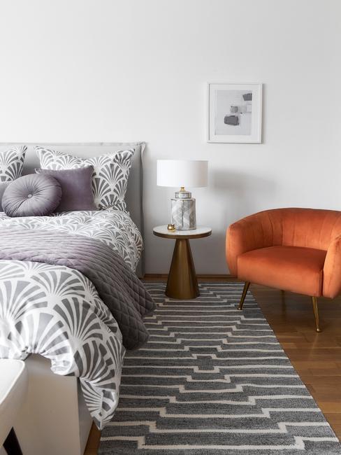 Biała sypialnia z pomarańczorym, czarno-białym dywanem oraz szarymi poduszkami na łóżku
