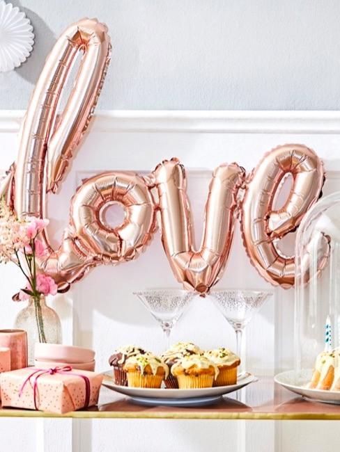 Tafeldecoratie voor babyparty met ballon, taartjes en cadeaus