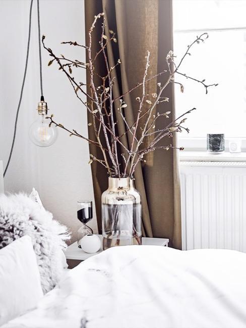 habitación blanca con cama blanca, jarrón decorativo y persianas de color marrón