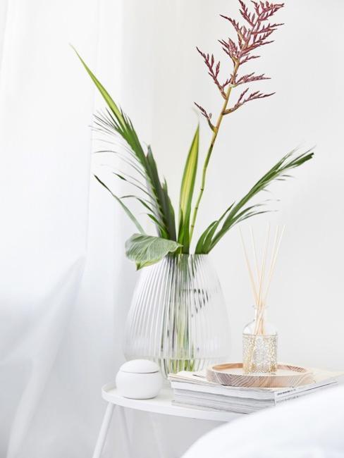 Mesa camilla con ambientador y un jarrón de cristal con una flor, en fondo blanco.