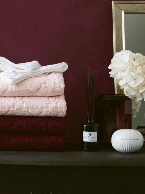 Estantería de madera con toallas rojas y rosas, ambientador y jarrón de cristal con flores blancas sobre fondo rojo