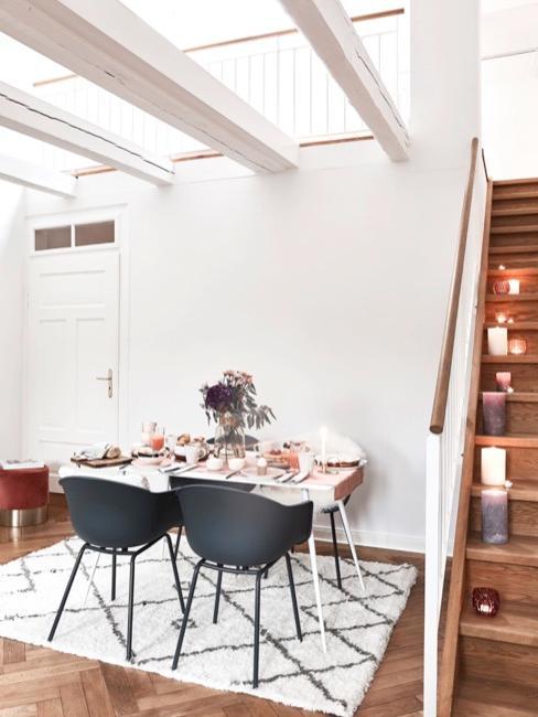 Loft inrichten eetkamer met zolderverdieping met zwarte stoelen en een eettafel naast de trap