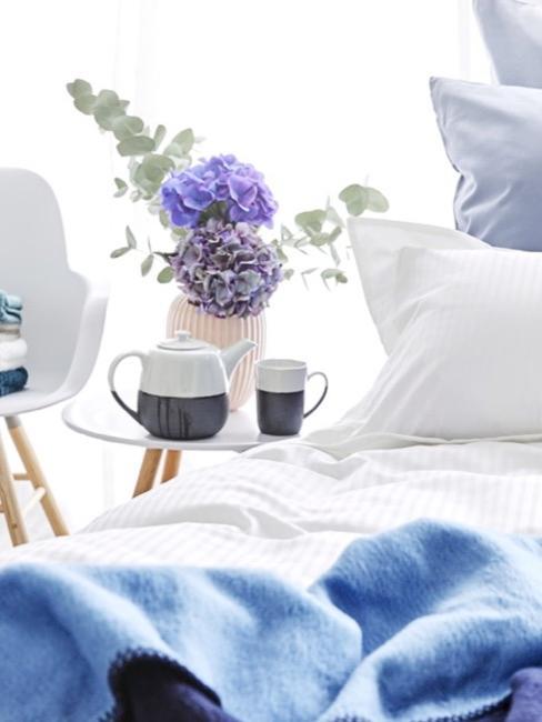 un jarrón con flores al lado de una cama