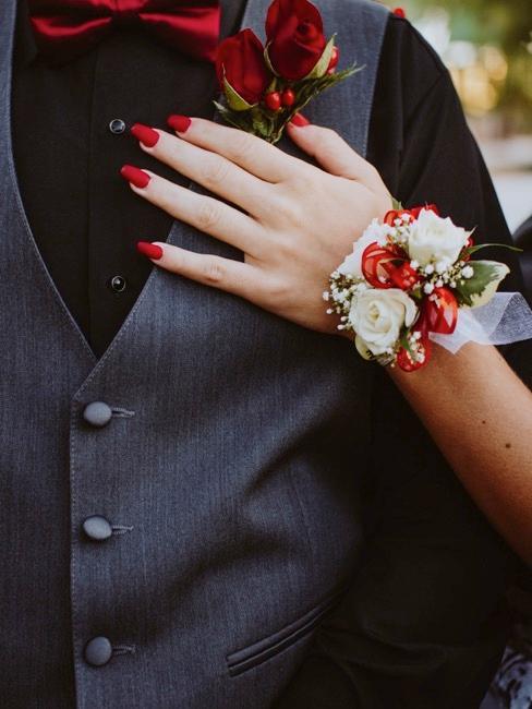 traje masculino y mano femenina con elementos rojos