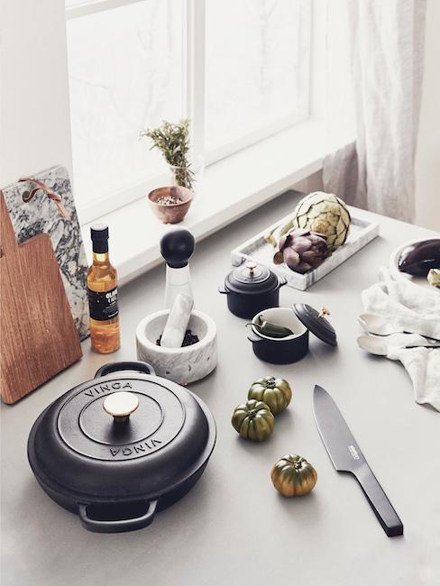 mesa de la cocina con accesorios de cocinar, un cuchillo y tomates