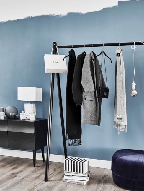 Pasillo pintado de azul claro con cómoda y perchero en madera oscura y lámpara blanca