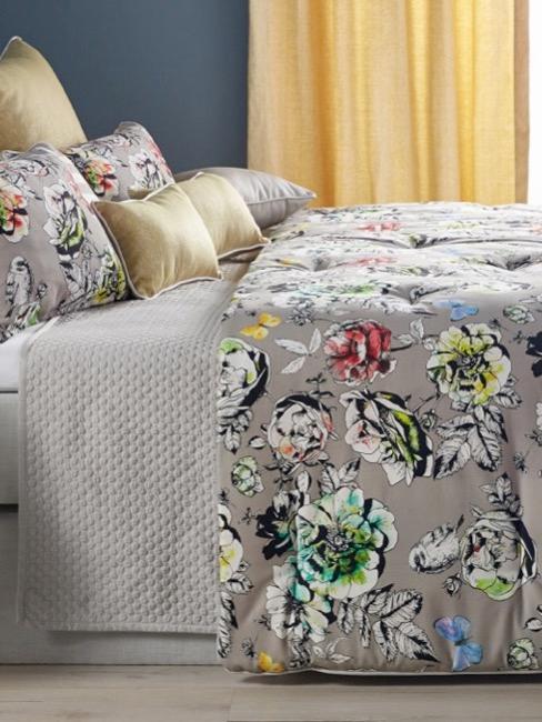 Chambre d'amis avec lit, table d'appoint et fleurs