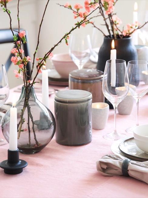 Glazen vaas naast een gewone vaas op tafel als tafeldecoratie naast kaarsen