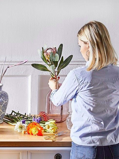 Eine blonde Frau dekoriert eine Vase mit einem bunten Blumenstrauß