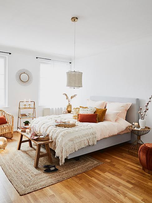 Slaapkamer in ethno stijl met grijs bed, houten bankje, gouden bijzettafel en ethno decoratie