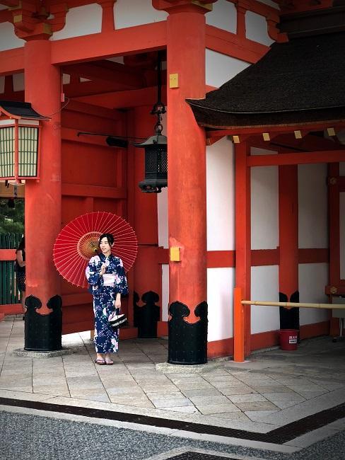 Japanische Frau in Shibori Kimono vor einem Haus