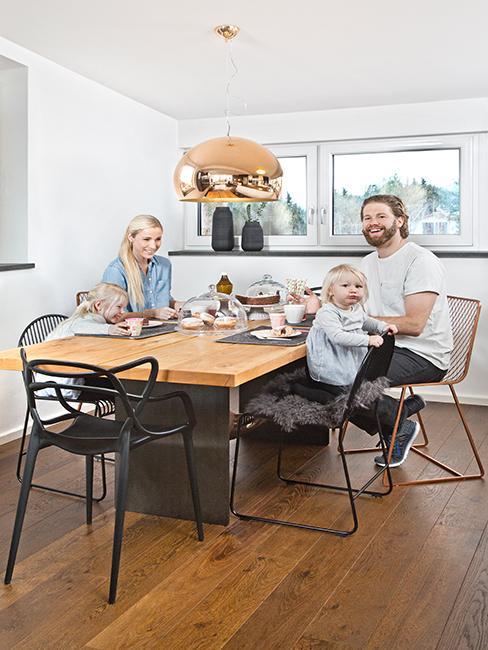 Vater, Mutter und Kinder sitzen am Esstisch und lachen