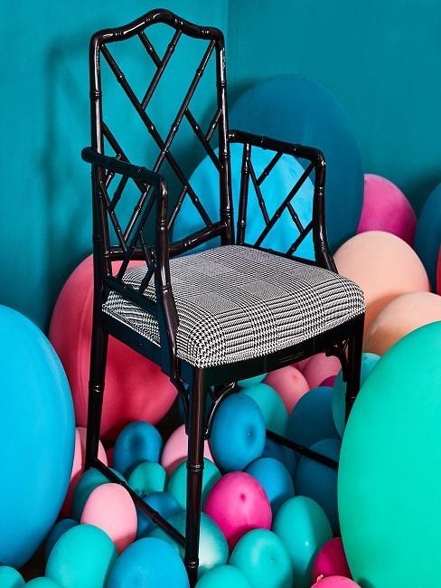 Stuhl inmitten lauter bunter Luftballons