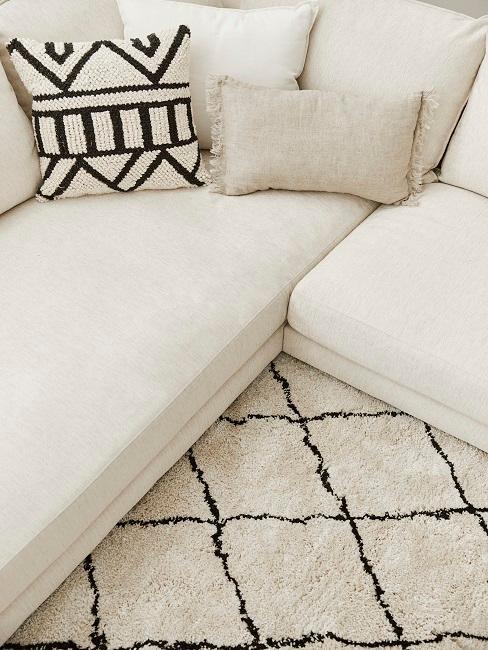 Ein beiges Sofa mit einem gemusterten Kissen auf einem schwarz-beige-gestreiftem Teppich
