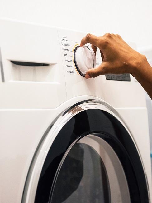 Wasmachine met vrouwelijke hand die aan de knop draait