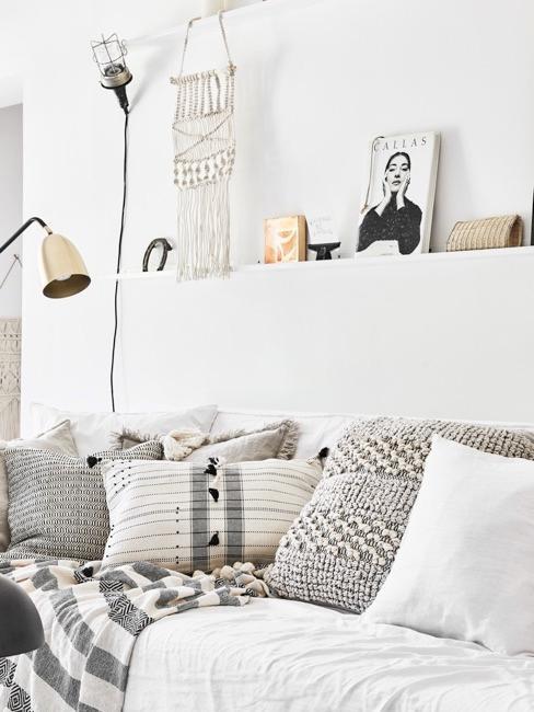 Makrama wisząca w jasnym salonie nad kanapą z szarymi, poduszkami dekoracyjnymi