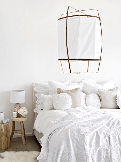 habitación blanca con un taburete como mesilla de noche