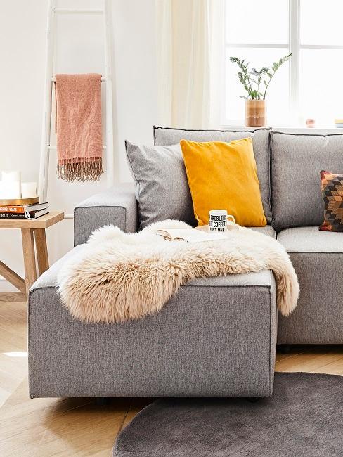 sofá gris con piel de oveja y un cojín amarillo