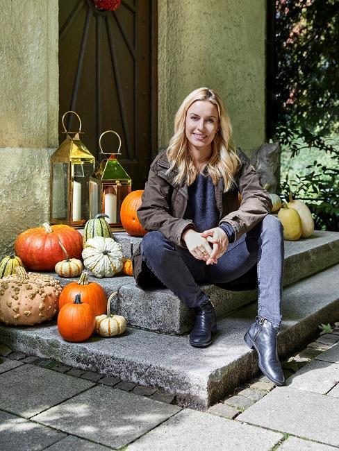 Westwing Gründerin Delia Fischer sitzt auf der Treppe im Hauseingang neben Kürbis Deko