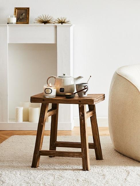 Hocker aus recyceltem Holz steht im Wohnzimmer mit einer Duftkerze und einer Kanne Tee mit passender Teetasse.