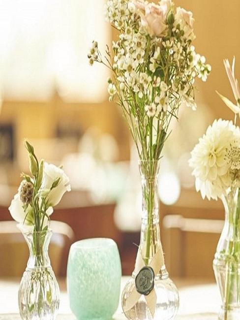 Vasen mit schönen Blumen auf dem Hochzeitstisch