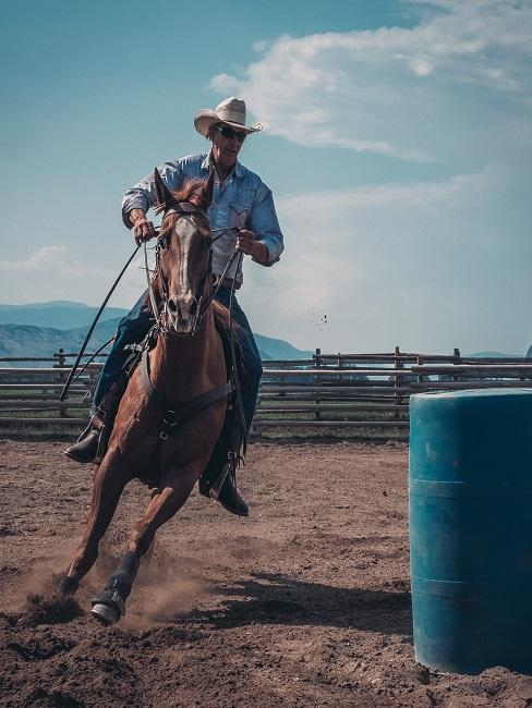Älterer Mann miz Cowboyhut auf einem Pferd galoppierend