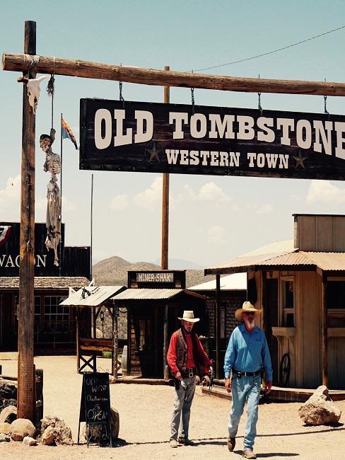 Zwei Männer mit Cowboyhut gehen aus einem Ort unter dem Schild Old Tombstone Western Town