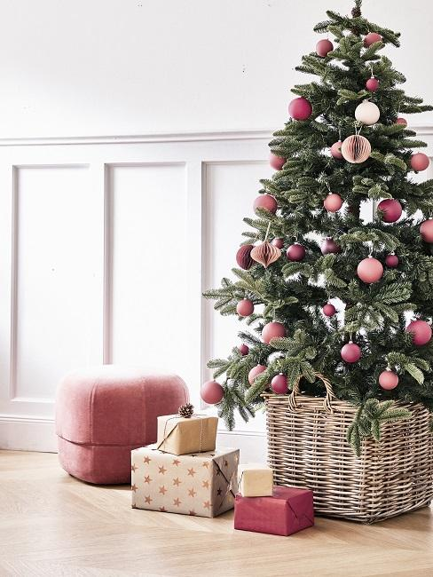 EIn geschmückter Weihnachtsbaum in einem hellen Raum, daneben ein Pouf und verpackte Geschenke