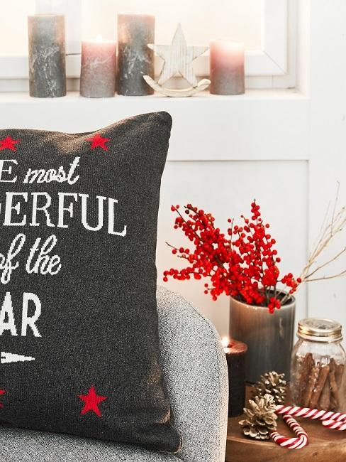 Sessel mit weihnachtlichem Kissen neben einem Beistellhocker aus Holz mit weihnachtlicher Deko und Tannenzapfen