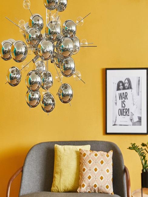 Lampe in Silber aus Kugelelementen vor einer gelben Wand mit 60er Style Bild und einem Sessel mit Sixties Deko-Kissen