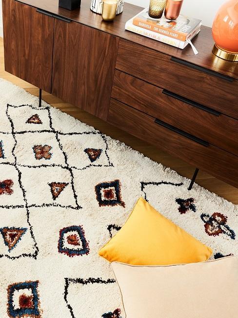 Gemusterter Teppich vor einem klassischen 60er-Sideboard aus Holz mit Deko und Büchern